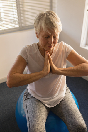 Photo pour High angle view of active senior woman performing yoga with ball exercice at home - image libre de droit