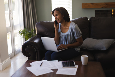 Photo pour Front view of woman talking on mobile phone while using laptop in living room at home - image libre de droit