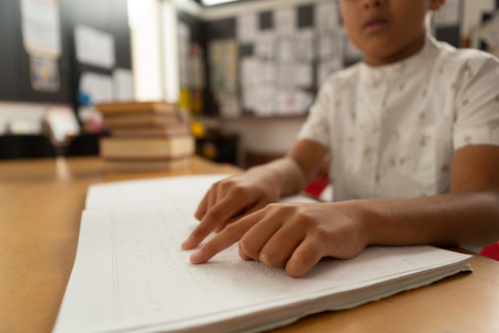 Photo pour Mid section of blind focused mixed-race schoolboy reading a braille book in classroom at elementary school - image libre de droit