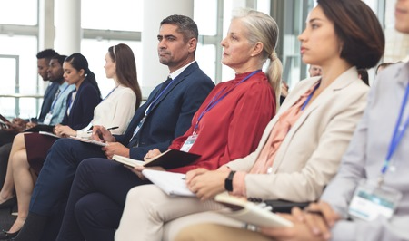 Photo for Side view of diverse business people looking serious while attending a business seminar in office building - Royalty Free Image