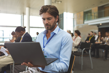 Photo for Front view of young Caucasian businessman using laptop during seminar in office building - Royalty Free Image