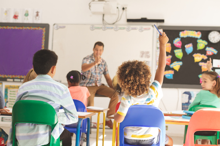 Foto de Rear view of school kids raising hand while teacher asking question in classroom at school - Imagen libre de derechos