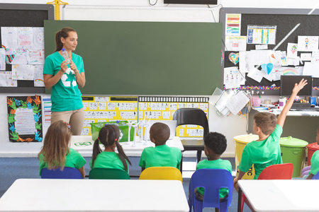Foto de Front view of caucasian teacher holding plastic bottle and standing in front of multi ethnic students discussing about green energy and recycle at desk in classroom - Imagen libre de derechos