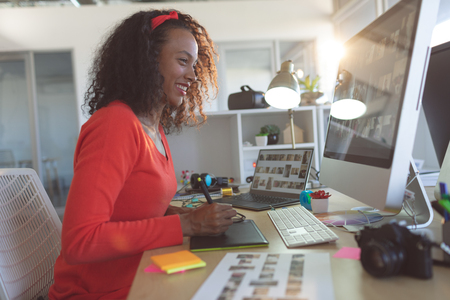 Foto für Side view of happy young mixed-race female graphic designer using graphic tablet at desk in a modern office - Lizenzfreies Bild