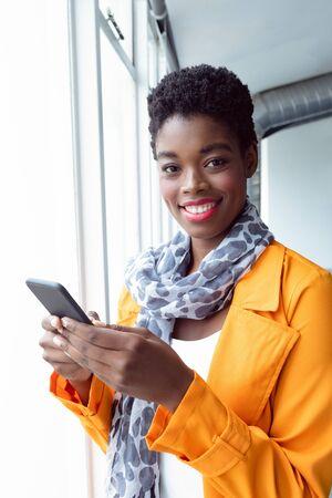 Photo pour Portrait of African-american Businesswoman using mobile phone near window in office - image libre de droit