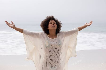 Foto de Front view of African american woman standing with arms outstretched on the beach - Imagen libre de derechos