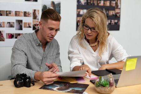 Foto für Front view of Caucasian male and female graphic designers discussing over photo at desk in office. This is a casual creative start-up business office for a diverse team - Lizenzfreies Bild