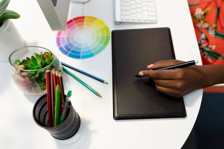 Foto für Mid section of African american female graphic designer using graphic tablet at desk in office. This is a casual creative start-up business office for a diverse team - Lizenzfreies Bild