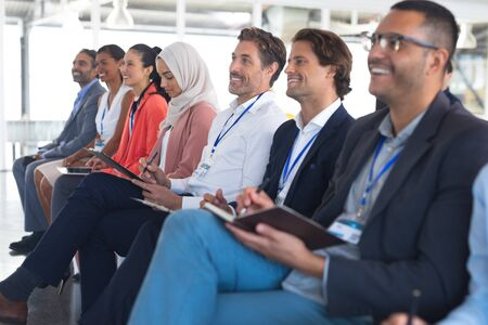 Photo for Side view of diverse happy audience listening to speaker in a business seminar. International diverse corporate business partnership concept - Royalty Free Image
