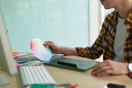 Foto für Mid section close-up of handsome Caucasian male graphic designer looking at color swatch at desk in office. New start-up business with entrepreneur working hard - Lizenzfreies Bild