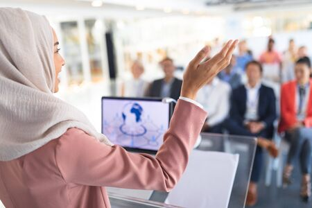 Photo pour Close-up of beautiful mixed-race female speaker in hijab giving speech in a business seminar. International diverse corporate business partnership concept - image libre de droit