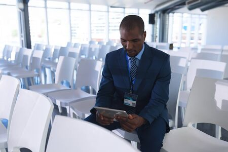 Foto de Front view of African-american Male speaker practicing his speech on digital tablet in business seminar at conference room. International diverse corporate business partnership concept - Imagen libre de derechos