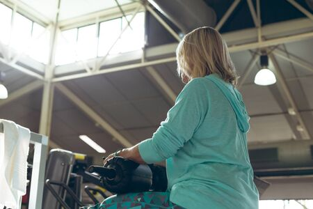 Photo pour Low angle view of disabled active senior Caucasian woman exercising with leg curl machine in fitness studio. Strong active senior female amputee training and working out - image libre de droit