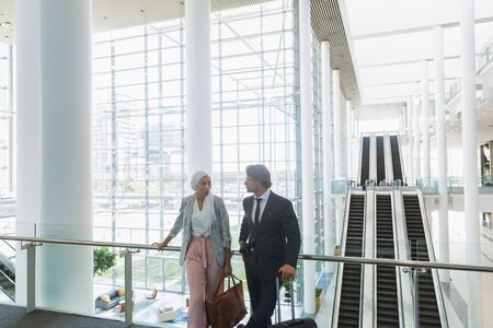 Foto de Front view of business people with bags talking with each other near railing in a modern office. Modern corporate start up new business concept with entrepreneur working hard - Imagen libre de derechos