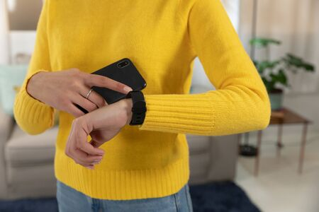 Foto per Front view mid section of a young Caucasian holding a smartphone and checking her smartwatch in her sitting room - Immagine Royalty Free