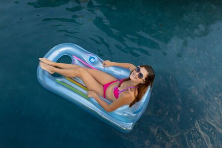 Photo for High angle view of a Caucasian woman wearing beachwear and sunglasses sitting on an inflatable pool lounger sunbathing in a swimming pool on a sunny day - Royalty Free Image