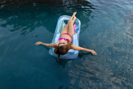 Photo for Rear view of a Caucasian woman wearing beachwear and sunglasses lying on an inflatable pool lounger sunbathing in a swimming pool on a sunny day, dipping her hands in the water - Royalty Free Image