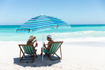 Foto de Rear view of a Caucasian couple sitting on deckchairs under the umbrella, on the beach with blue sky and sea in the background, smiling, looking at each other and making a toast - Imagen libre de derechos