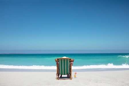 Foto de Rear view of a senior African American woman on a beach in the sun, sitting in a deckchair, resting and looking out to sea, blue sky in the background - Imagen libre de derechos