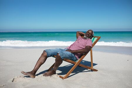 Foto de Front view of a senior African American man on a beach, sitting in a deckchair, resting and looking to camera - Imagen libre de derechos