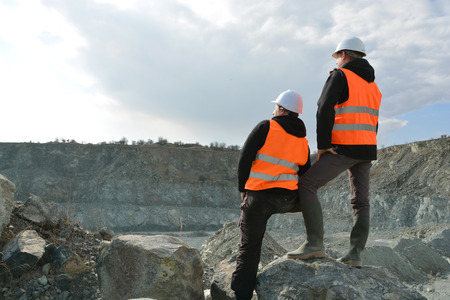 Photo pour Two workers and quarry in background - image libre de droit