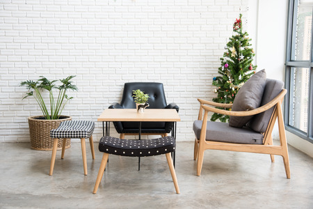 cozy sofa corner with christmas tree decoration at the back. sofa is in modern style and made with wood.