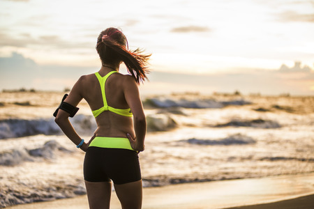 Foto de young healthy lifestyle woman running at sunrise beach - Imagen libre de derechos