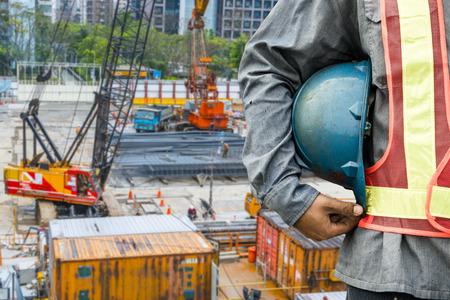 Photo pour construction worker checking location site with crane on the background - image libre de droit
