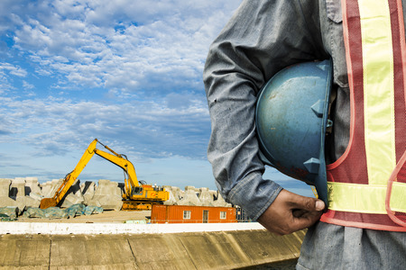 Photo pour construction worker checking location site with crane on the background - image libre de droit