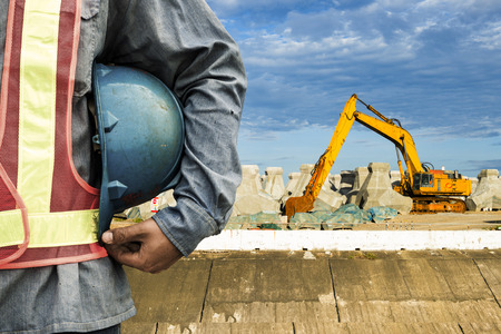 Foto per construction worker checking location site with crane on the background - Immagine Royalty Free