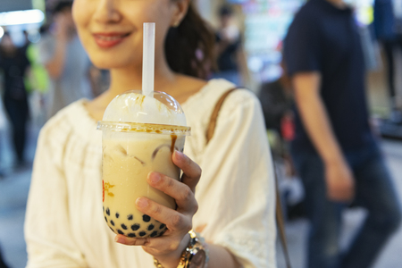 Photo pour Woman drinks pearl milk tea at Taiwan night market - image libre de droit