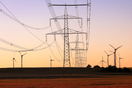 Photo pour Green energy concept - high voltage power lines with a windmill farm background - image libre de droit