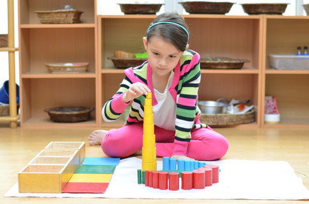 Photo pour Little girl hand building tower made of montessori educational materials - image libre de droit
