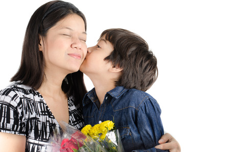 Little boy kissing his mother with flower on white background
