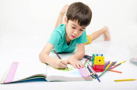 Foto de Little boy coloring image lay on th floor - Imagen libre de derechos