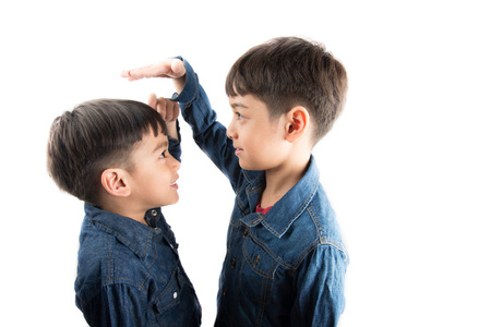 Foto de Little sibling boy brothers checking there tall each other - Imagen libre de derechos