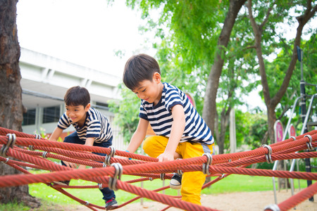 Photo pour Little boy climbing rope at plaground - image libre de droit