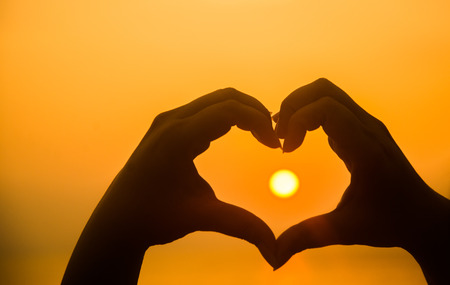 Photo pour hand making heart shape over sunset - image libre de droit