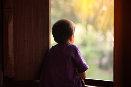 Little boy standing alone looking out of the window