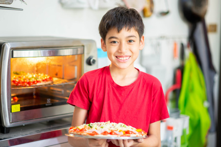 Photo pour Little boy cooking pizza homemade in the kitchen at home - image libre de droit