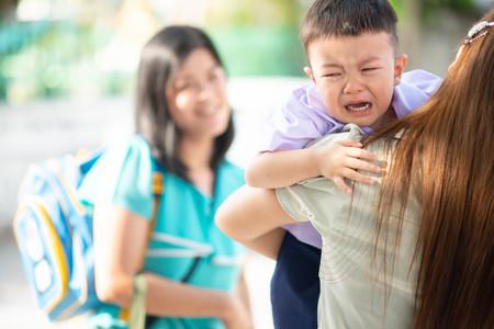 Foto de Little toddler boy cry, first day at school kindergarten with mother - Imagen libre de derechos