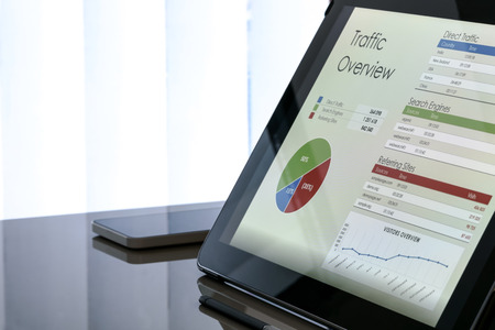 Foto de Charts and data on the tablet screen with smartphone next to the window at the office - Imagen libre de derechos