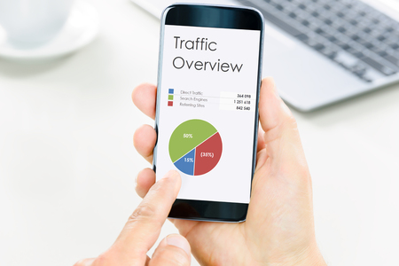 Foto de Modern digital marketing concept - businessman holds a smartphone and analyzes digital data and charts. - Imagen libre de derechos