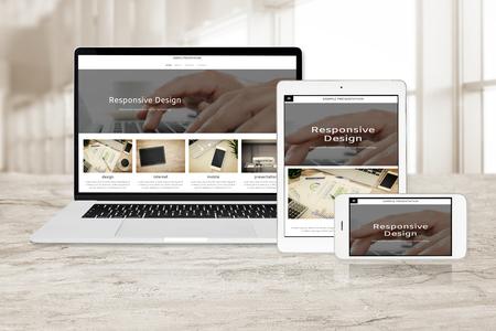 Foto de Concept image of multi device technology for responsive web design - laptop , digital tablet and smartphone in various orientation at the office (sample web page). - Imagen libre de derechos