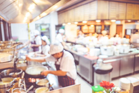 Foto de Blurred background : Groups of Chef cooking in the open kitchen,customer can see they cooking at food counter, cooking chef with light bokeh - Imagen libre de derechos