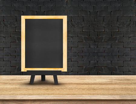 Photo pour Menu blackboard on  Wooden Table top at black brick wall,Template mock up for display of your product,Business presentation. - image libre de droit