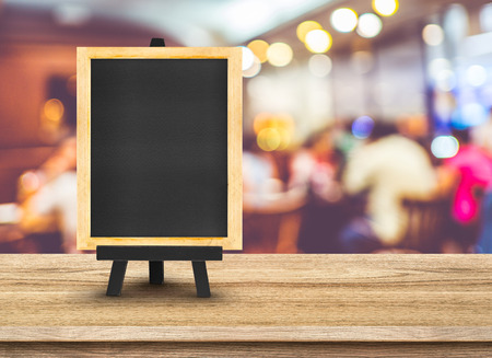 Photo pour Blackboard menu with easel on wooden table with blur restaurant background, Copy space for adding your content. - image libre de droit