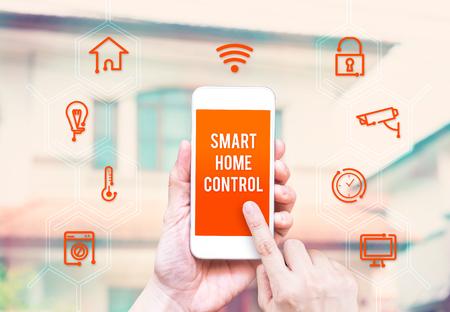 Foto de Hand holding smart phone with home control application with blur home background, Smart home concept. - Imagen libre de derechos
