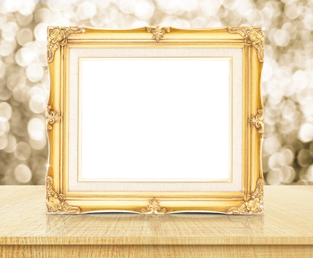 Photo pour Blank golden vintage photo frame with sparkling gold bokeh wall and wooden table. - image libre de droit