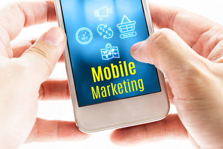 Foto de Close up Two hand holding smart phone with Mobile Marketing word and icons, Digital concept. - Imagen libre de derechos